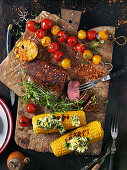 Grilled meat, corn cobs and tomato skewers