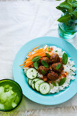 A turquoise plate with meatballs, tomatoe sauce and mint rice, garnished with slices of cucumber and carrots
