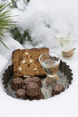 Mini chocolate Bundt cakes, honey cake and pear schnapps on a vintage tart tin in the snow