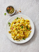 Tagliatelle with garlic and basil pesto, walnuts, pine nuts and basil leaves