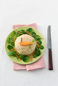 A fish cake decorated with carrots and capers with lamb's lettuce