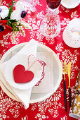 Festive place setting with heart decoration on a red and white tablecloth