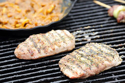 Grilled pork neck steaks and onions in barbecue sauce