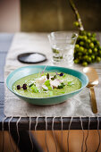 Cream of pea soup with pesto, cod and micro greens