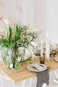 Table set for wedding with vase of tulips, dry twigs and pillar candles