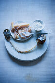 Smoked fish with sour cream on a serving platter with a fish carcass in front of it
