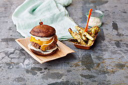 A burger with courgette chips and a chilli dip