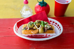 Hot Dog with pork sausage with roast potatoes, a fresh basil pesto and sour cream