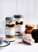 Ingredients for baking cookies: oatmeal, cranberries and white chocolate chips in glass jars
