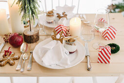 Christmas place setting with gingerbread mousse in glass bowl and guest favours in red-and-white striped boxes