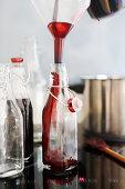 Elderberry juice being poured into glass bottles