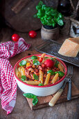Pasta penne with pepper, tomato sauce and bacon
