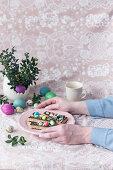 Woman holding plate with Mazurek (No bake Polish Easter cake)