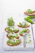 Crostini with garlic and pea cream and stracciatella cheese