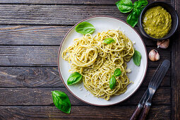 Spaghetti pasta with homemade pesto sauce over wooden background
