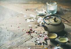 Traditional Asian tea ceremony arrangement with iron teapot, cups, dried rose buds and candles
