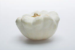 A pale patty-pan squash on a white surface