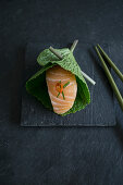 Nigiri sushi with salmon in a fresh wasabi leaf