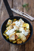 Fish fillets on fried potatoes with herb quark in a pan