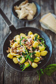 Gnocchi with spinach and mushrooms in a pan
