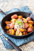 Fried potatoes with sausage in a cast iron pan