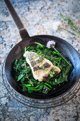 Hake on sauteed spinach in a frying pan