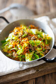 Nappa cabbage and shredded carrots with ground sausage in a pan