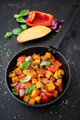Sweet potato, sweet peppers, and red onion in a pan