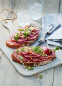 Two slices of bread with salami on a light wooden board