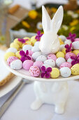 Colourful sugar eggs on white presentation plate with Easter bunny motif