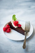 Dark chocolate cake with fresh whipped cream, fresh berries on white plates