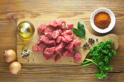 Raw ingredients with beef goulash on a wooden surface