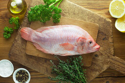 A whole raw rosefish with ingredients on a wooden surface