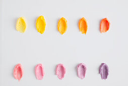 Cupcake frosting in yellow, orange, pink and purple tones