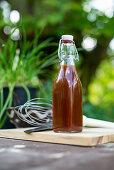 Flasche mit selbstgemachter Barbecuesauce in der Gartenküche
