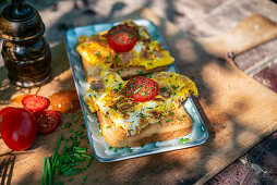 Toast with scrambled eggs, tomatoes and chives on a garden table