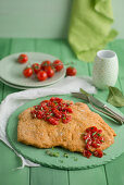 Giant schnitzel with caramelised cherry tomatoes