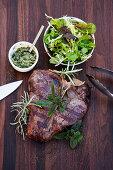 Grilled T-bone steak with salsa verde and a wild herb salad