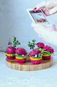 Mini vegan burgers with beetroot, carrots and lettuce being photographed