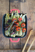 Baked celery stalks with grilled tomatoes and crispy bacon
