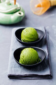 Matcha ice cream scoop in bowl on a grey stone background