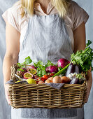 Woman holding basket with fresh ingredients