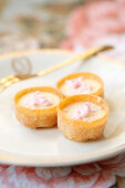 Mini tarts filled with cream and pink meringues on a glass plate