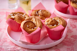 Small puff pastry brioches in pink paper cups