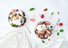 Healthy breakfast - Berry crumble with fresh blueberries, raspberries, strawberries, walnuts, pecans, yogurt, and mint