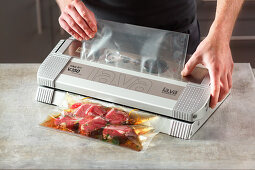 Meat and juices being vacuum packed without air intake