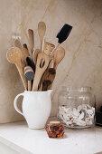 Various kitchen utensils in ceramic jug