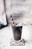 Vegan milkshake with coconut milk, charcoal and ice cubes