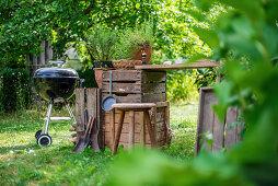 A garden kitchen with a round grill in a summer garden