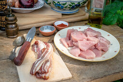 Pork and bacon with spices and oil on a wooden table